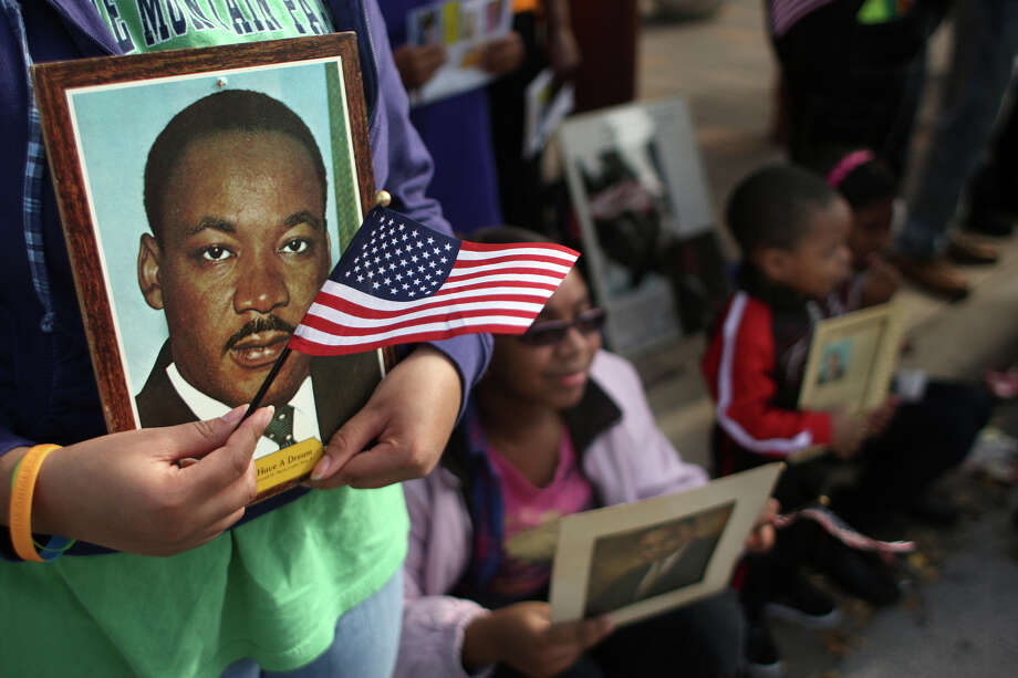 Paige Freels, 13, holds a picture of Dr. Martin Luther King Jr. during the Black Heritage Society's 36th Annual Original Martin Luther King Jr. Parade downtown Monday, Jan. 20, 2014, in Houston. Photo: Johnny Hanson, Houston Chronicle / © 2014  Houston Chronicle