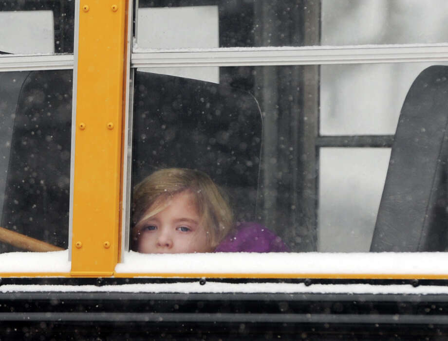 A girl peers out the window of a Greenwich School bus on Bruce Park Avenue during the snowstorm that hit Greenwich, Conn., Tuesday afternoon, Jan. 21, 2014. The Greenwich Public Schools had an early release due to the storm. The National Weather Service is forecasting a foot of snow for Greenwich by the time the storm ends early Wednesday morning. Photo: Bob Luckey / Greenwich Time