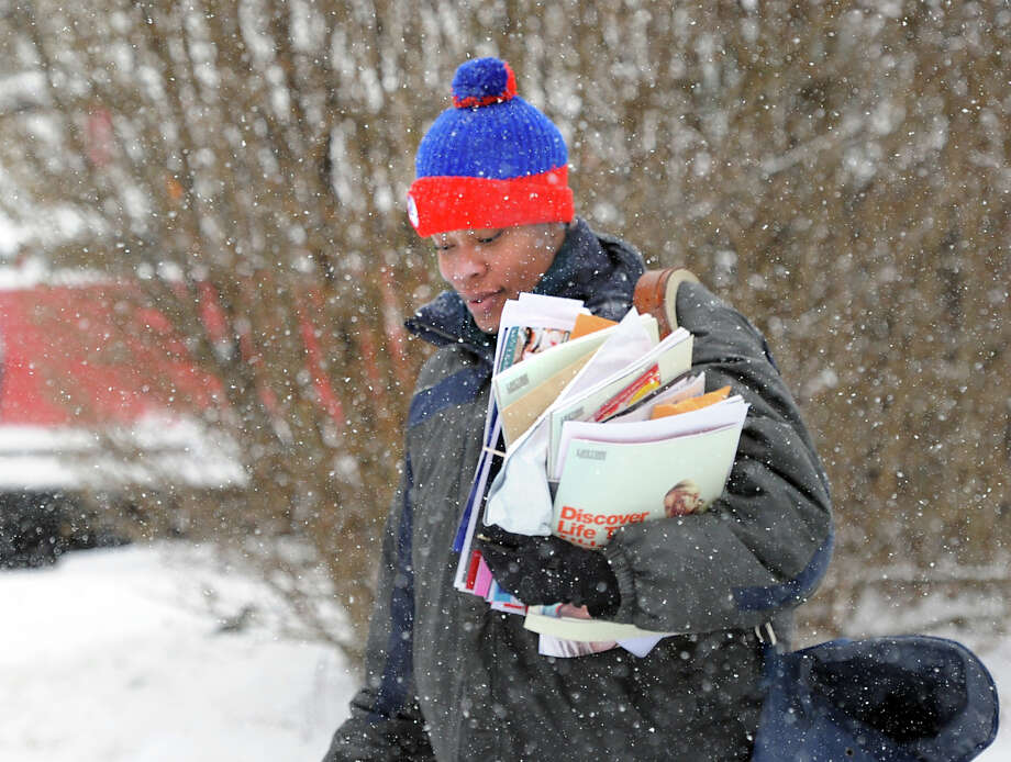 U.S. Postal carrier Tahiyyah Taylor delivers mail on Sherman Avenue during the snowstorm that hit Greenwich, Conn., Tuesday afternoon, Jan. 21, 2014. The National Weather Service is forecasting a foot of snow for Greenwich by the time the storm ends early Wednesday morning. Photo: Bob Luckey / Greenwich Time