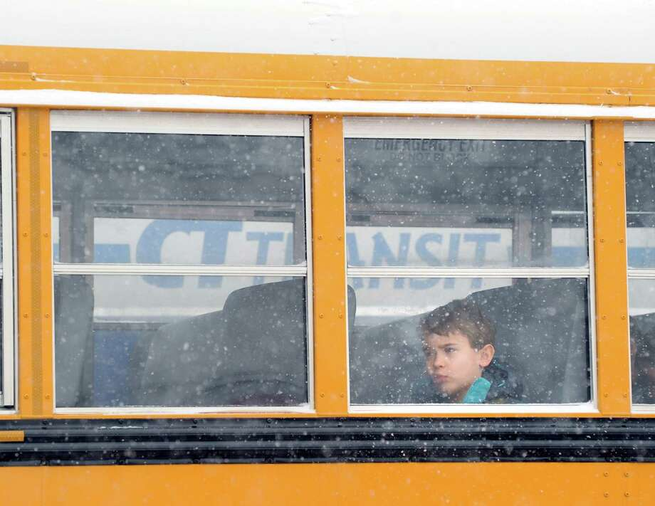 A boy peers out the window of a Greenwich School bus on Bruce Park Drive during the snowstorm that hit Greenwich, Conn., Tuesday afternoon, Jan. 21, 2014. The Greenwich Public Schools had an early release due to the storm. The National Weather Service is forecasting a foot of snow for Greenwich by the time the storm ends early Wednesday morning. Photo: Bob Luckey / Greenwich Time