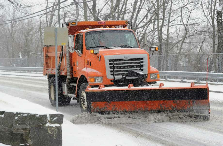 A plow truck clears snow from Byram Road during the snowstorm that hit Greenwich, Conn., Tuesday afternoon, Jan. 21, 2014. The National Weather Service is forecasting a foot of snow for Greenwich by the time the storm ends early Wednesday morning. Photo: Bob Luckey / Greenwich Time