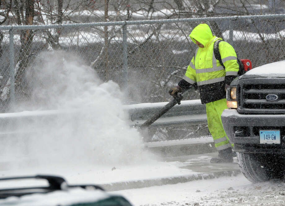 Town of Greenwich DPW worker Rashadd Hill uses a blower to clear snow from the Byram Road sidewalk during the snowstorm that hit Greenwich, Conn., Tuesday afternoon, Jan. 21, 2014. The National Weather Service is forecasting a foot of snow for Greenwich by the time the storm ends early Wednesday morning. Photo: Bob Luckey / Greenwich Time
