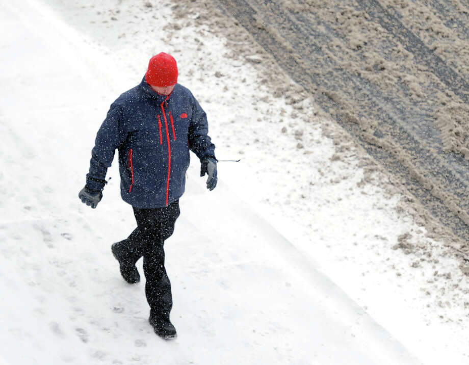 A pedestrian walks on Steamboat Road during the snowstorm that hit Greenwich, Conn., Tuesday afternoon, Jan. 21, 2014. The National Weather Service is forecasting a foot of snow for Greenwich by the time the storm ends early Wednesday morning. Photo: Bob Luckey / Greenwich Time