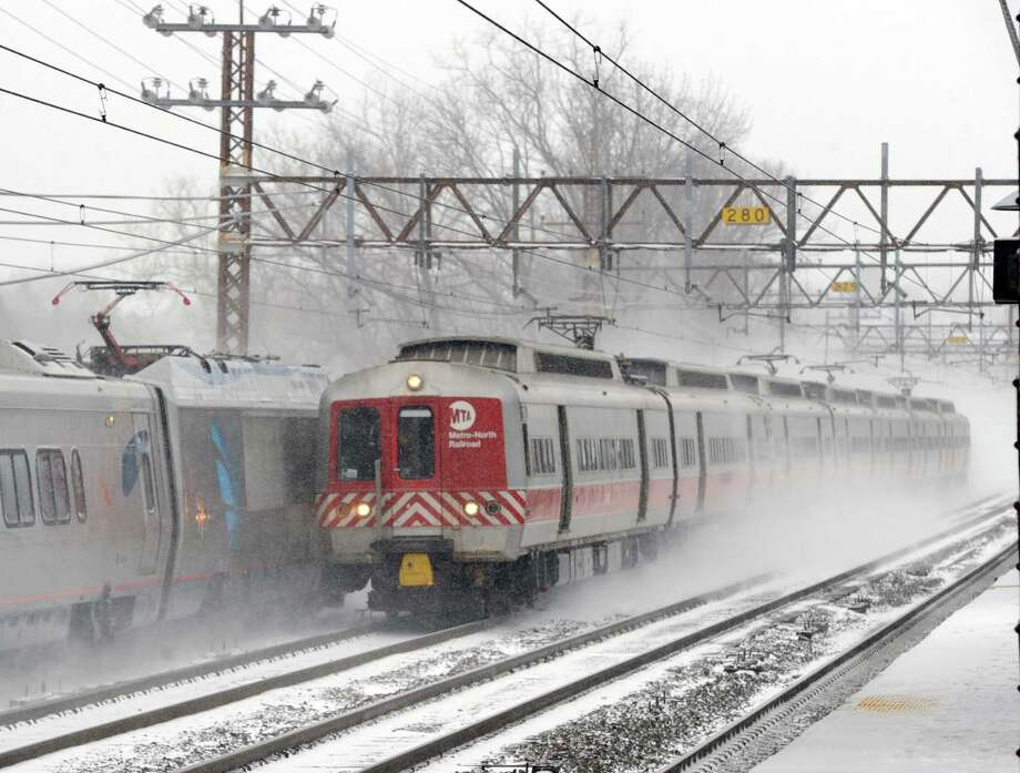 A Metro-North train makes its way in the snowstorm passing through the Central Greenwich Train Station in Greenwich, Conn., Tuesday afternoon, Jan. 21, 2014. The National Weather Service is forecasting a foot of snow for Greenwich by the time the storm ends early Wednesday morning. Photo: Bob Luckey / Greenwich Time