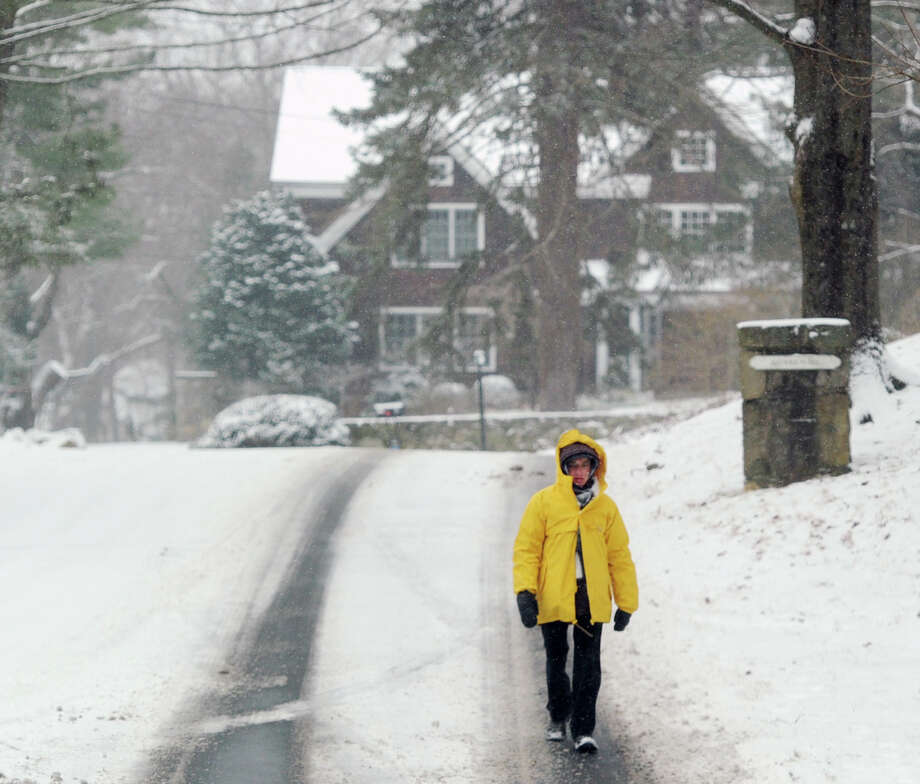 A woman walks on Anderson Road during the snowstorm that hit Greenwich, Conn., Tuesday afternoon, Jan. 21, 2014. The National Weather Service is forecasting a foot of snow for Greenwich by the time the storm ends early Wednesday morning. Photo: Bob Luckey / Greenwich Time