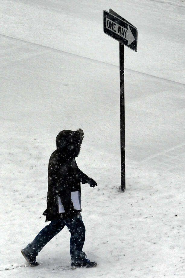A lone pedestrian walks in the snow near South Frontage Road, in Bridgeport, Conn. Jan. 21, 2014. Photo: Ned Gerard / Connecticut Post