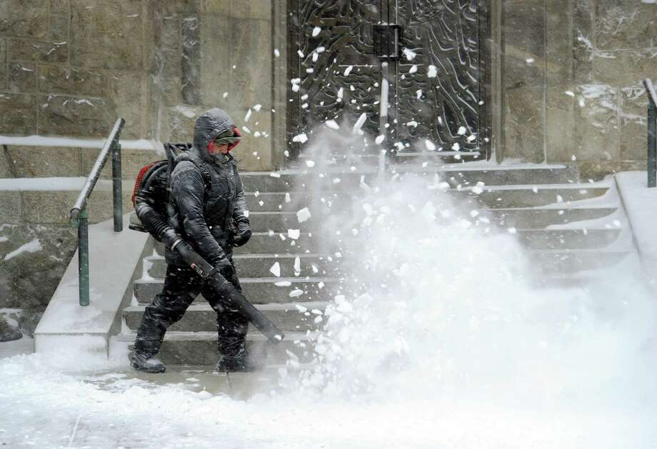 Victor Nivicela snow blows the steps at sidewalks at St. Peter Church on Main Street in Danbury, Conn, during Tuesday's snow storm, January 21, 2014. Photo: Carol Kaliff / The News-Times
