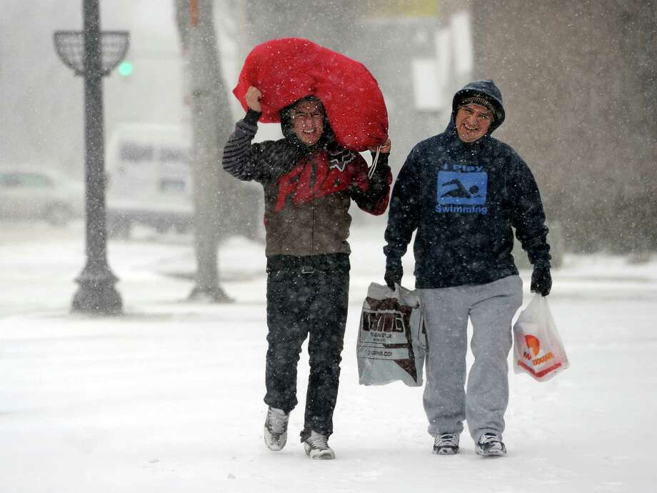 Two men walk down Main Street in Danbury, Conn. in a snowstorm, Tuesday, January 21, 2014. Photo: Carol Kaliff / The News-Times