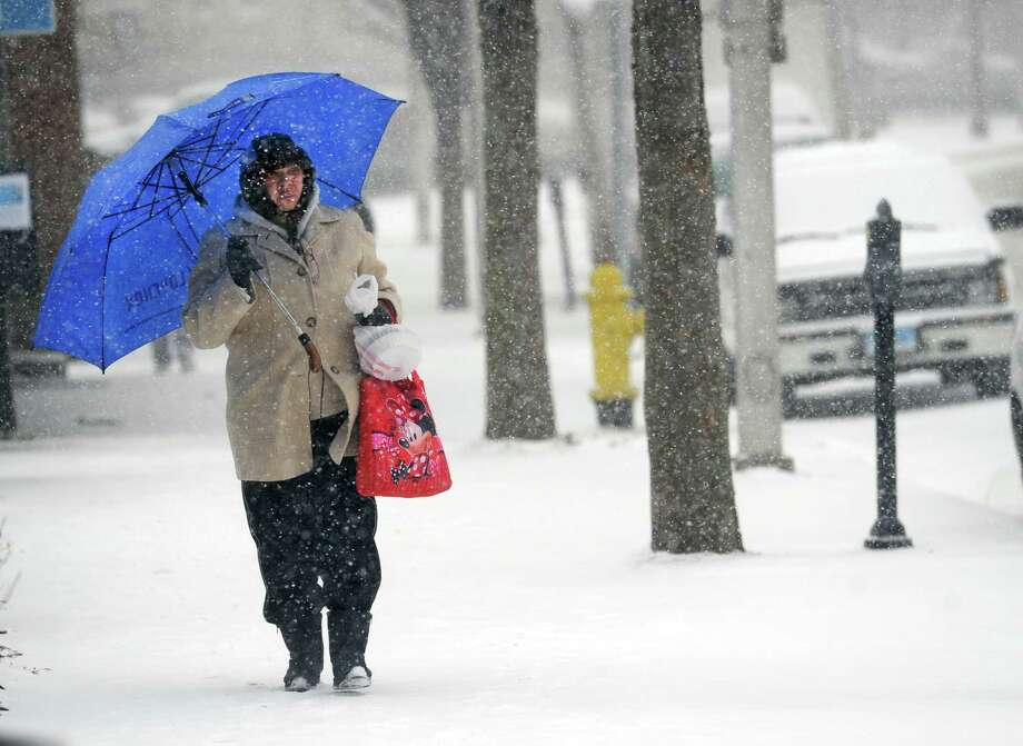 A woman walks down Main Street in Danbury, Conn. in the snow Tuesday, January 21, 2014. Photo: Carol Kaliff / The News-Times