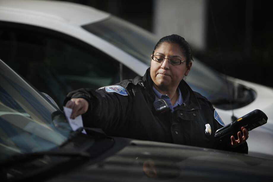 Municipal Transportation Agency parking control officer Karla Colindres slips a parking citation under  a windshield wiper of a car on Van Ness Avenue. Parking tickets generate $88 million a year for the city. Photo: Lea Suzuki, The Chronicle