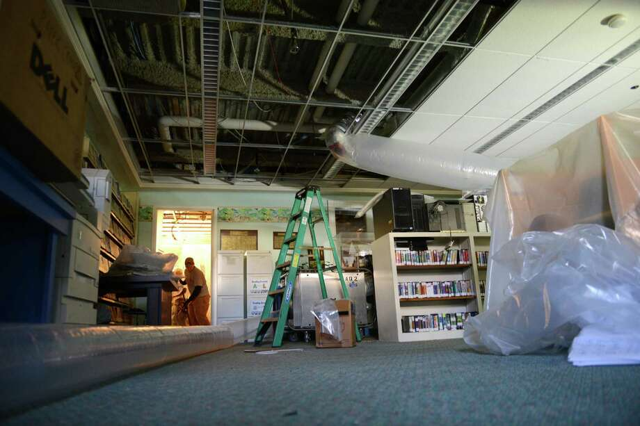 In this file photo from January 8, Library employees, volunteers and water damage experts are work to repair the extensive water damage at the C.H. Booth Library in Newtown, Conn. The damage occurred when a sprinkler pipe on the third floor burst, causing water to rush to the floors below and collapsing the ceiling in the process. Photo: Tyler Sizemore / The News-Times