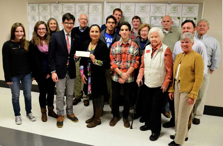 Shekaiba Wakili-Bennett, co-chair of the United Nations Committee of New Canaan, holds a $1,000 check the organization donated to the New Canaan High School Model U.N. Club on Friday, Jan. 10, at the high school in New Canaan, Conn. Members of the committee and the club, pictured above, came to the school to learn about the students' upcoming trip to The Hague International Model U.N. conference. Photo: Nelson Oliveira / New Canaan News