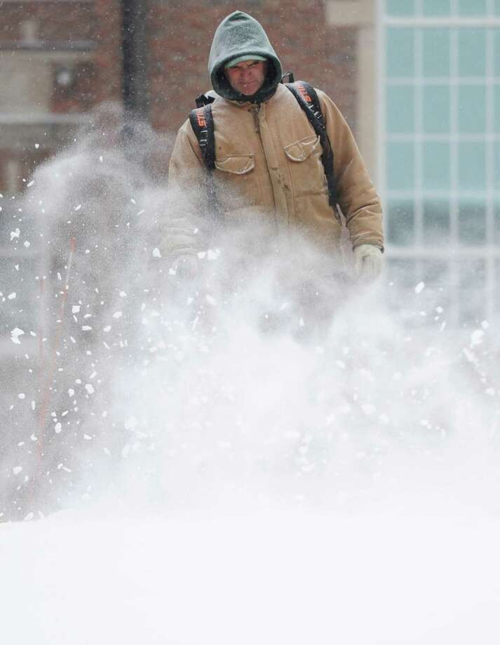 Newtown Parks and Recreation employee Will Jacobs blows snow off the sidewalk at the Fairfield Hills Campus in Newtown, Conn. Tuesday, Jan. 21, 2014.  The area is expected to get six to 10 inches as the snow continues through Wednesday morning. Photo: Tyler Sizemore / The News-Times