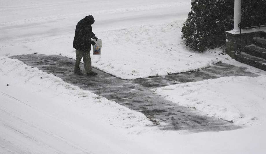 A man salts the sidewalk near the Western Connecticut campus as snow falls in Danbury, Conn. Tuesday, Jan. 21, 2014.  The area is expected to get six to 10 inches as the snow continues through Wednesday morning. Photo: Tyler Sizemore / The News-Times