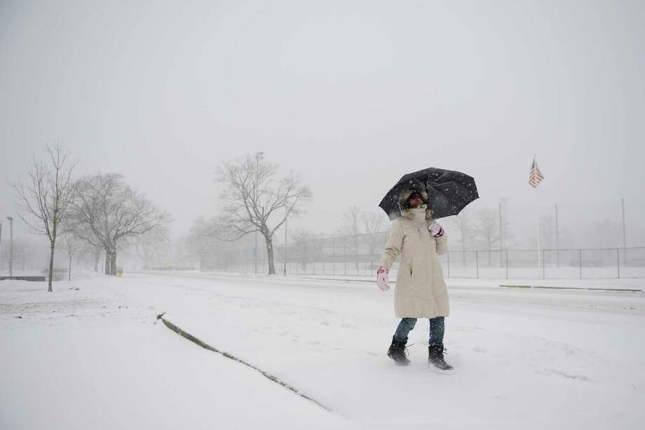 Brigitte Martinez, of Danbury, walks with an umbrella as snow falls in Danbury, Conn. Tuesday, Jan. 21, 2014.  The area is expected to get six to 10 inches as the snow continues through Wednesday morning. Photo: Tyler Sizemore / The News-Times