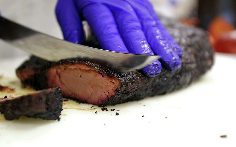 Professor Jeff Savell slices a smoked brisket during Foodways Texas and Texas A&M University's Camp Brisket at the university's Rosenthal Meat Science & Technology Center Friday Jan. 10, 2014, in College Station. Camp Brisket focuses smoked brisket, covering topics such as grades/types of beef, types of smokers and more.  ( James Nielsen / Houston Chronicle ) Photo: James Nielsen, Staff / © 2013  Houston Chronicle