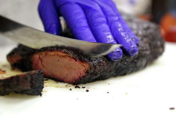 Professor Jeff Savell slices a smoked brisket during Foodways Texas and Texas A&M University's Camp Brisket at the university's Rosenthal Meat Science & Technology Center Friday Jan. 10, 2014, in College Station. Camp Brisket focuses smoked brisket, covering topics such as grades/types of beef, types of smokers and more.  ( James Nielsen / Houston Chronicle )