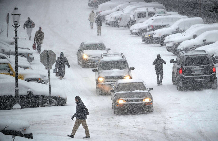 Commuters trudge through a snowy parking lot to their cars at the Fairfield train station in Fairfield, Conn. on Tuesday, January 21, 2014. Photo: Brian A. Pounds / Connecticut Post