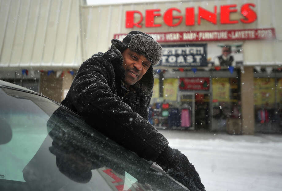 Jean Jacquet, of Bridgeport, wipes snow from his windshield in a parking lot on Boston Avenue in Bridgeport, Conn. on Tuesday, January 21, 2014. Photo: Brian A. Pounds / Connecticut Post