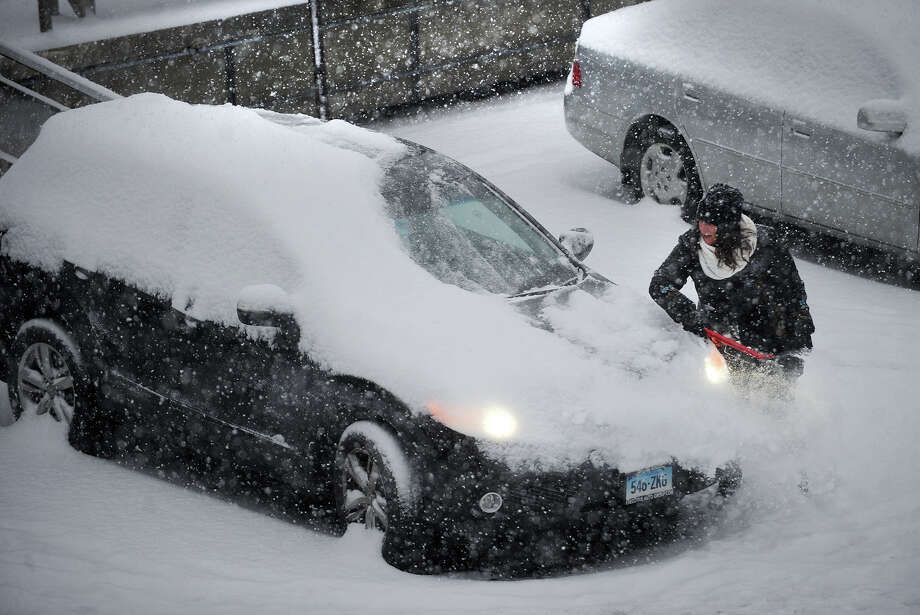A woman clears snow from her car at the train station in Fairfield, Conn. during the snowstorm on Tuesday, January 21, 2014. Photo: Brian A. Pounds / Connecticut Post