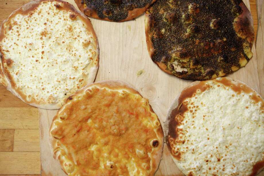 Cedars Bakery offers a variety of cheese bread, left, kafta, top, and za'atar pies. Photo: Eric Kayne / Eric Kayne