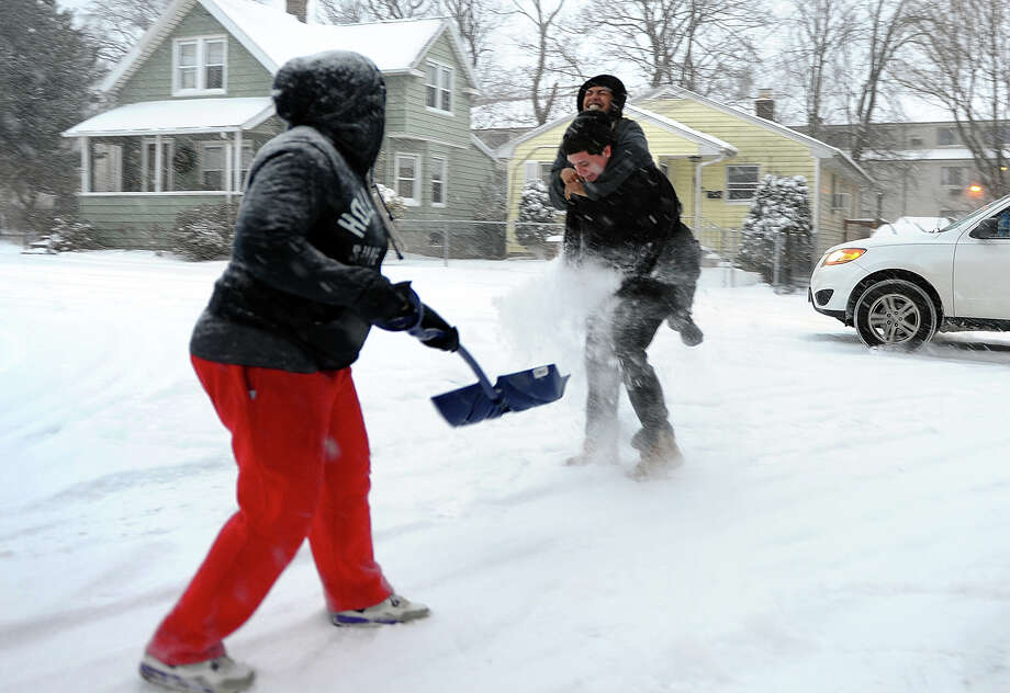 Diane Gonzales tosses snow onto her friends Moises Castro, top, and Marco Amador, during the snowstorm on Howard Street in Stratford, Conn. on Tuesday January 21, 2014. Photo: Christian Abraham / Connecticut Post