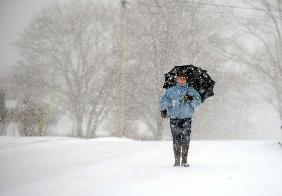 Carlos Garcia, of Derby, walks toward Sentinel Hill in Derby, Conn. Tuesday, Jan. 21, 2014 to meet his wife at the bottom of the hill to drive her car up the slick road. Photo: Autumn Driscoll / Connecticut Post