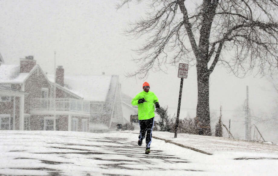 A jogger stands out in the near white-out conditions along Morningside Drive in Milford, Conn. during a snowstorm pounding the region on Tuesday January 21, 2014. Photo: Christian Abraham / Connecticut Post