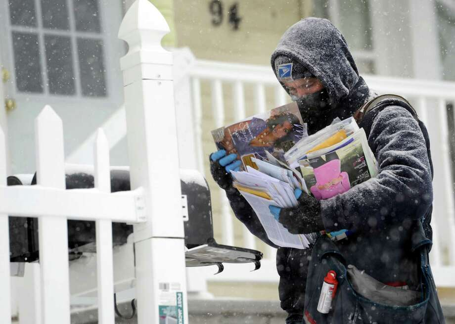 Tim Dwyer, a U.S. postal worker, delivers mail on Liberty Street in Danbury, Conn., during Tuesday's snowfall, January 21, 2014. Photo: Carol Kaliff / The News-Times