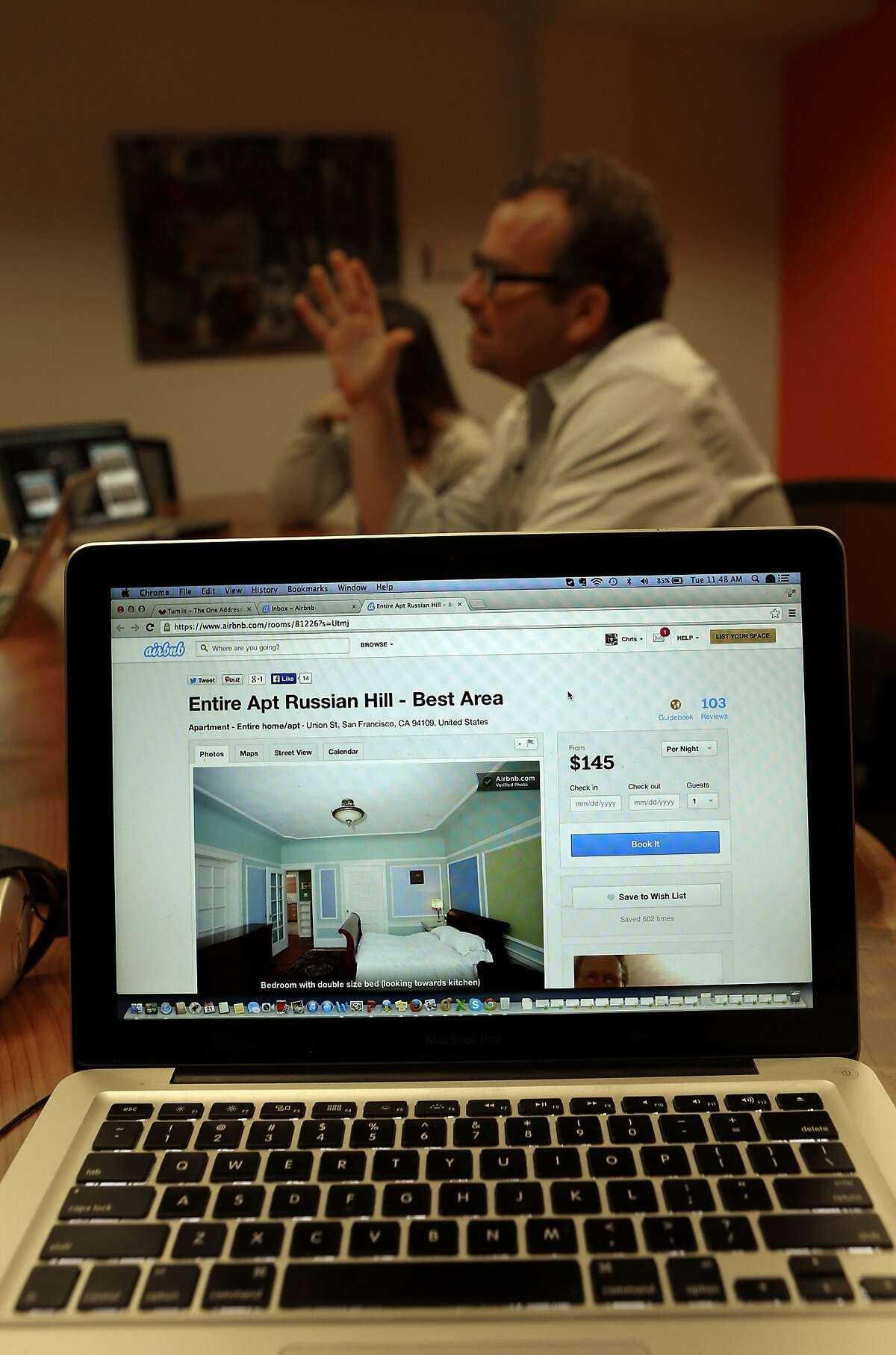 A listing for a unit in Chris Butler's former apartment building is shown on the website of AirBnB as Butler speaks with colleagues as his place of work, on Tuesday Jan. 21, 2014. Butler is Chief Operating Officer of Tumlis, a real estate for sale start up company in San Francisco, Calif. He was evicted from his Union Street apartment where he had lived for the past ten years and now his landlord is now renting it out on AirBnB.