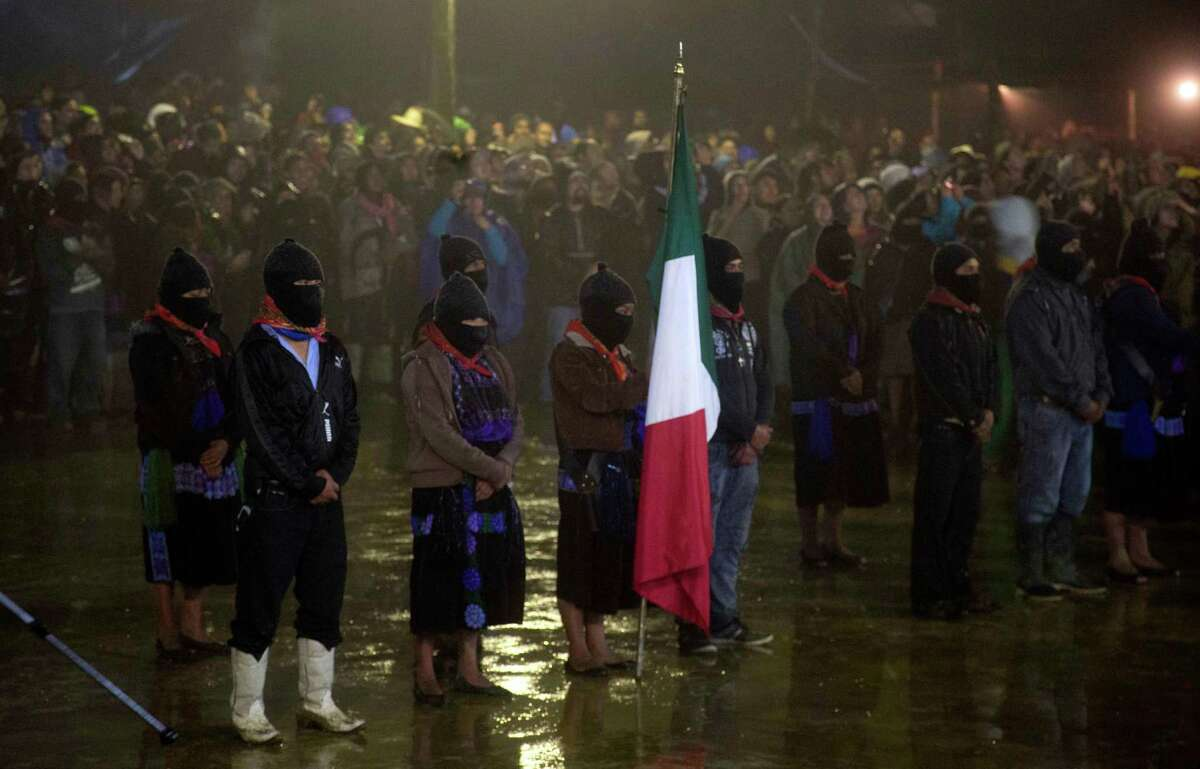 Masked members of the Zapatista National Liberation Army, EZLN, stand at attention, one holding Mexico's national flag, at an event marking the 20th anniversary of the Zapatista uprising in the town of Oventic, Chiapas, Mexico, late Tuesday, Dec. 31, 2013. The Zapatistas waged a brief armed uprising in the name of Indian rights in January of 1994. Since then, the rebels have waged a relatively peaceful resistance from the jungles of Chiapas. (AP Photo/Eduardo Verdugo)