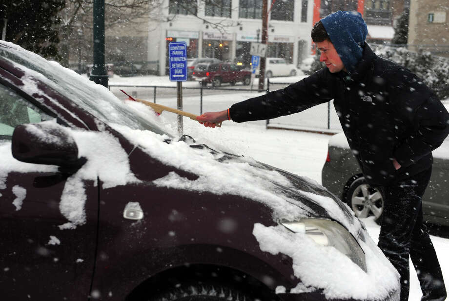 Nicholas Abriola gets the snow off of his car after his shift at Milford Photo in downtown Milford, Conn. on Tuesday January 21, 2014. Photo: Christian Abraham / Connecticut Post