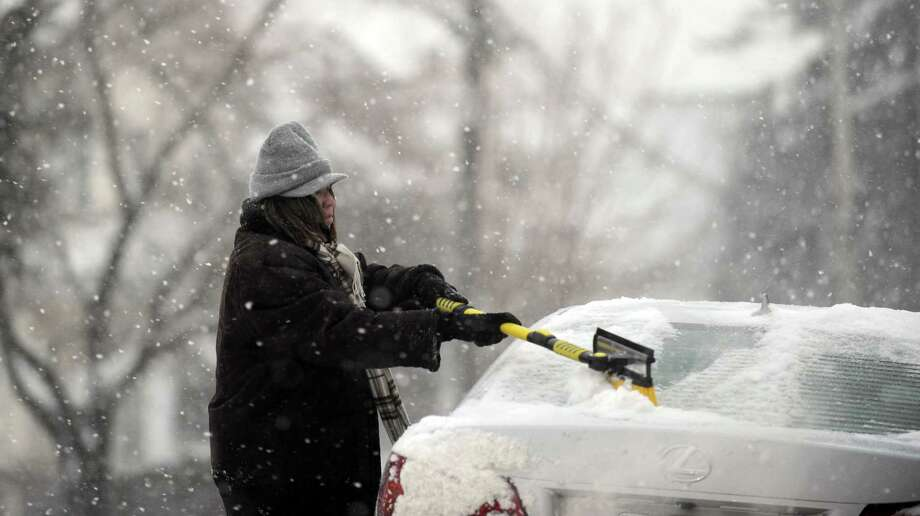 Peg Healy, of Seymour, clears the snow off her car as she gets ready to leave work in Derby, Conn. Tuesday, Jan. 21, 2014. Photo: Autumn Driscoll / Connecticut Post