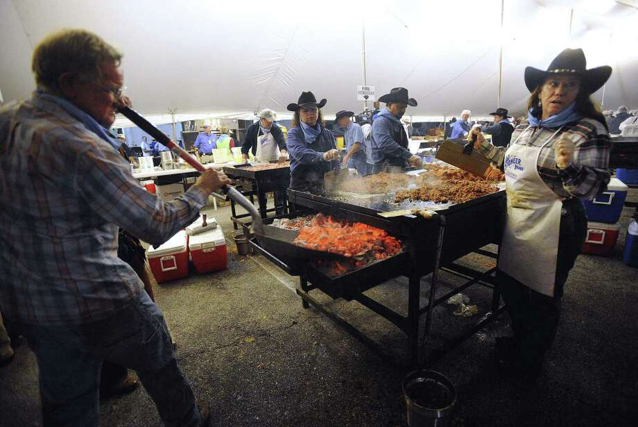 Dickie Dziuk, left, delivers glowing briquets as Sarah Mosher, right, prepares ground beef for tacos during the 2013 Cowboy Breakfast at Cowboys Dancehall. Photo: File Photo / San Antonio Express-News / SAN ANTONIO EXPRESS-NEWS