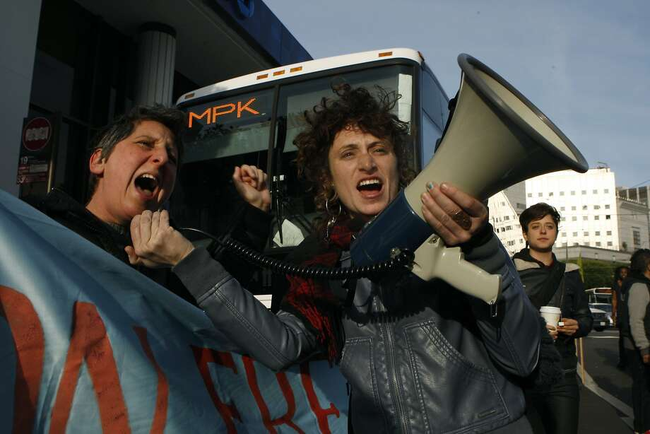 Sara Shortt (left) from the Housing Rights committee of San Francisco and activist Erin McElroy (right) block a Facebook bus heading to Menlo Park on 8th at Market streets in San Francisco, Calif., on Tuesday, January 22, 2014.  The San Francisco Metropolitan Transportation Agency votes on  an 18-month pilot plan allowing Google buses to use designated Muni bus stops to pick up and drop off tech commuters to Silicon Valley. Photo: Liz Hafalia, The Chronicle