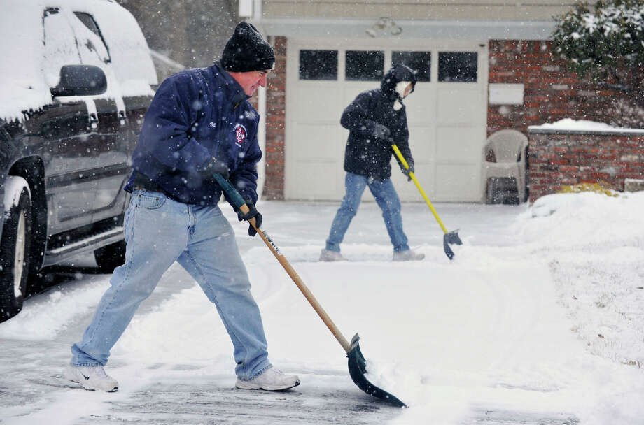 Bill Avalos, left, and his wife, Jane, shovel their son's driveway in Stamford, Conn., on Tuesday, Jan. 21, 2014. The Avalos' are visiting from Florida to see their grandchildren. Bill is a retired Stamford Fire Department captain. Photo: Jason Rearick / Stamford Advocate