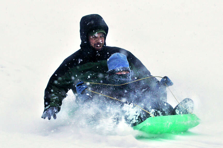 Sean Flood sleds down a hill with his son, Jackson, at Brennan Golf Course in Stamford, Conn., on Tuesday, Jan. 21, 2014. Photo: Jason Rearick / Stamford Advocate