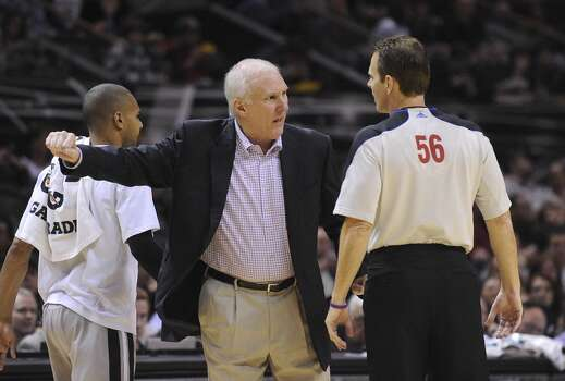 San Antonio Spurs coach Gregg Popovich questions a  all as official Mark Ayotte listens during NBA action against the Portland Trailblazers in the AT&T Center on Friday, Jan. 17, 2014. Photo: Billy Calzada, San Antonio Express-News