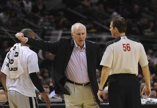 San Antonio Spurs coach Gregg Popovich questions a call as official Mark Ayotte listens during NBA action against Portland in the AT&T Center on Friday, Jan. 17, 2014. Photo: Billy Calzada, San Antonio Express-News