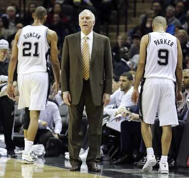 San Antonio Spurs coach Gregg Popovich gives instructions to the team against the New Orleans Pelicans as San Antonio Spurs' Tim Duncan and San Antonio Spurs' Tony Parker walk off the court during first half action Monday Nov. 25, 2013 at the AT&T Center. Photo: Edward A. Ornelas, San Antonio Express-News