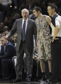 San Antonio Spurs head coach Gregg Popovich talks with Nando De Colo during the second half against the Washington Wizards at the AT&T Center, Wednesday, Nov. 13, 2013. The Spurs won 92-79. Photo: Jerry Lara, San Antonio Express-News