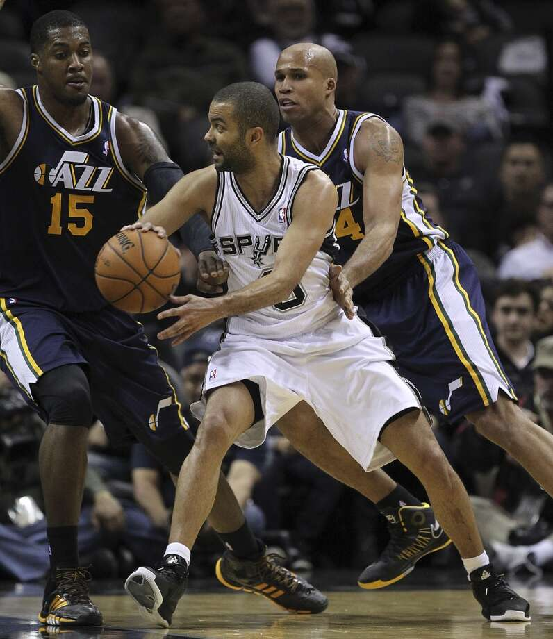 San Antonio Spurs' Tony Parker passes around Utah Jazz' Derrick Favors, left, and Richard Jefferson during the first half at the AT&T Center, Wednesday, Jan. 15, 2014. Photo: Jerry Lara, San Antonio Express-News