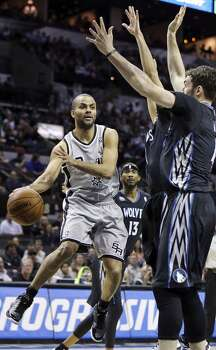 San Antonio Spurs' Tony Parker passes around Minnesota Timberwolves' Ricky Rubio and Kevin Love during first half action Sunday Jan. 12, 2014 at the AT&T Center. Photo: Edward A. Ornelas, San Antonio Express-News