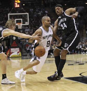Spurs' Tony Parker (09) gets fouled while driving to the basket by Brooklyn Nets' Andrei Kirilenko (47) in the second half at the AT&T Center on Tuesday, Dec. 31, 2013. Spurs win 113-92. Photo: Kin Man Hui, San Antonio Express-News