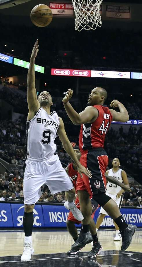 San Antonio Spurs' Tony Parker shoots around Toronto Raptors' Chuck Hayes during first half action Monday Dec. 23, 2013 at the AT&T Center. Photo: Edward A. Ornelas, San Antonio Express-News