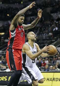 San Antonio Spurs' Tony Parker looks for room under Toronto Raptors' Amir Johnson during second half action Monday Dec. 23, 2013 at the AT&T Center. The Spurs won 112-99. Photo: Edward A. Ornelas, San Antonio Express-News
