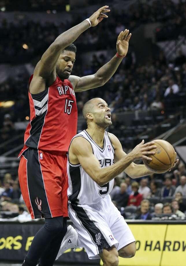 San Antonio Spurs' Tony Parker looks for room under Toronto Raptors' Amir Johnson during second half action Monday Dec. 23, 2013 at the AT&T Center. The Spurs won 112-99. Photo: Edward A. Ornelas, San Antonio Express-News