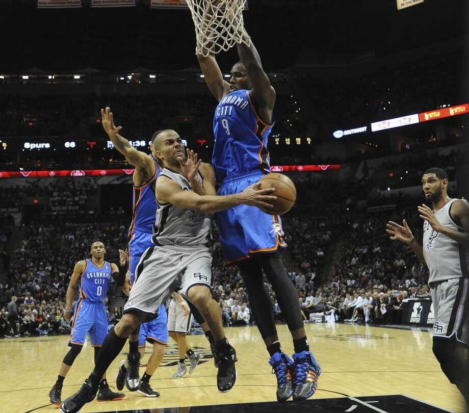 The Spurs' Tony Parker dishes off an assist to teammate Tim Duncan as Serge Ibaka of the Thunder defends during second-half NBA action at the AT&T Center on Saturday, Dec. 21, 2013. Oklahoma City won the game, 113-100. Photo: Billy Calzada, San Antonio Express-News