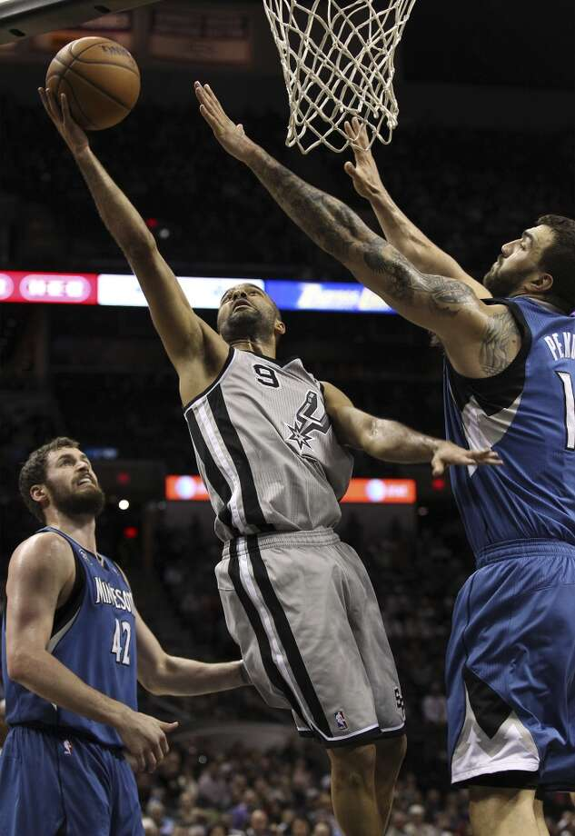 Spurs' Tony Parker (09) slices to the basket between Minnesota Timberwolves' Kevin Love (42) and Nikola Pekovic (14) in the first half at the AT&T Center on Friday, Dec. 13, 2013. Photo: Kin Man Hui, San Antonio Express-News
