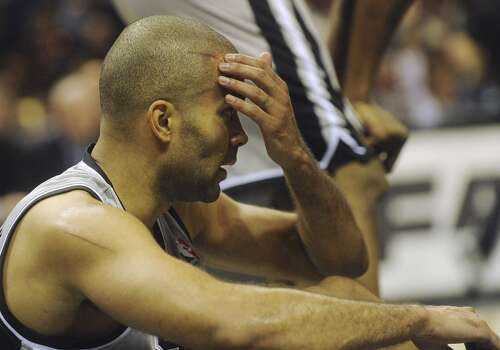 Tony Parker of the San Antonio Spurs reaches for a cut on his head after he was fouled during second-half NBA action in the AT&T Center on Saturday, Dec. 7, 2013. Photo: Billy Calzada, San Antonio Express-News